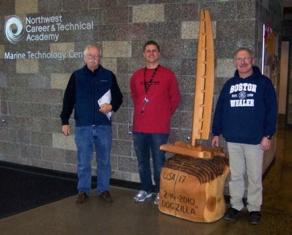 Anacortes Museum Director Steve Oakley delivers 'DoGilla' to Hunter Ware and Wes Fridell of th